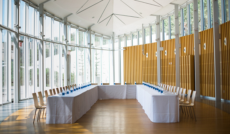 Tables are set up for an event at The Atrium at Brooklyn Botanic Garden