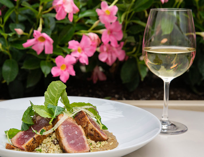 Seared tuna with a glass of white wine served outdoors at The Sea Grill in NYC