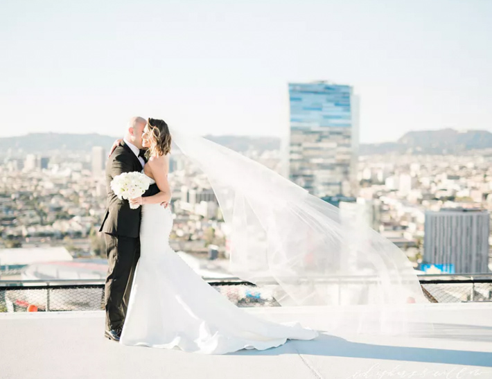 Bride and groom embrace on top of South Park Center in downtown Los Angeles