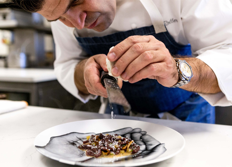 Chef grates cheese over a dish served at Patina Restaurant in Los Angeles
